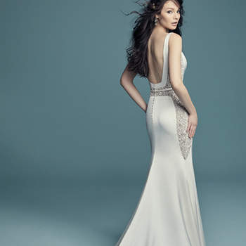 """<a href=""""https://www.maggiesottero.com/maggie-sottero/fabienne/11472"""">Maggie Sottero</a>  This whimsical yet sophisticated Orlando Satin wedding gown features intricate beading on sheer tulle along the waist and side panels—a modern twist on a vintage-inspired sheath silhouette. Complete with bateau neckline and square back. Finished with attached Orlando Satin belt and crystal buttons over zipper closure. Tulle veil accented in pearls and Swarovski crystals (Charlene, VL8MS694) sold separately."""