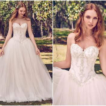 """Koronkowe motywy na klatce piersowej z Keela Mikado wyglądają cudownie w tej sukni ślubnej w stylu księżniczki, z małym dekoltem, baskinką w tali i tiulową spódnicą niczym z balowej sukni. Pod spodem wykrojowana, aby dać wrażenie dopasowanego kroju. Wykończone kryształowymi guzikami.  <a href=""""https://www.maggiesottero.com/maggie-sottero/benton/11155?utm_source=zankyou&amp;utm_medium=gowngallery"""" target=""""_blank"""">Maggie Sottero</a>"""