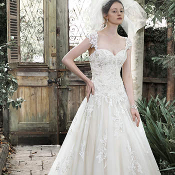 """Elegance and romance combine to create this dreamy ball gown. Exquisite lace, accented with pearl embellishments, adorns a fitted bodice before flaring into a voluminous tulle skirt, edged in delicate lace. Complete with sweetheart neckline, optional lace cap-sleeves and corset closure. <a href=""""https://www.maggiesottero.com/maggie-sottero/dallasandra/9278"""" target=""""_blank"""">Maggie Sottero</a>"""