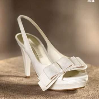 Des sandales blanches à semelles compensées avec un gros noeud à l'avant. Source : Pronovias 2012