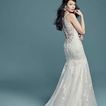 """<a href=""""https://www.maggiesottero.com/maggie-sottero/november/11499"""">Maggie Sottero</a>  Beaded lace motifs cascade over tulle in this romantic wedding dress, completing the halter neckline with illusion plunge. Complete with illusion back accented in lace motifs and tulle fit-and-flare skirt. Finished with crystal buttons over zipper closure."""