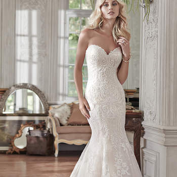 """Lovely in lace, this fit and flare wedding dress is the epitome of beauty with bold lace appliqués laying atop tulle, cascading to a subtly flared skirt. Finished with sweetheart neckline and corset closure. Detachable lace cap-sleeves sold separately. <a href=""""www.maggiesottero.com/maggie-sottero/rosamund/9524"""" target=""""_blank"""">Maggie Sottero</a>"""