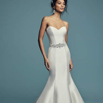 """<a href=""""https://www.maggiesottero.com/maggie-sottero/cassidy/11460"""">Maggie Sottero</a>  Simple yet glamorous, this Felicity Mikado wedding dress features a strapless sweetheart neckline and crystal buttons trailing from back neckline to hem. Lined with shapewear for a figure-flattering fit. Finished with zipper closure. Illusion off-the-shoulder jacket accented in vintage-inspired beading and Swarovski crystals sold separately. Beaded belt accented in Swarovski crystals sold separately."""