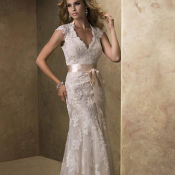 """A dreamy lace and tulle slim line gown with V-neckline and cap-sleeves features a separate slip gown of Vogue Satin to be worn below. The alluring open back is finished with a covered button over zipper closure. Includes a detachable satin ribbon belt. <a href=""""http://www.maggiesottero.com/dress.aspx?style=12623"""" target=""""_blank"""">Maggie Sottero</a>"""