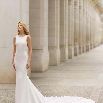 Simplicidade e sedução. É assim o vestido Tarac, com corpete simples e justo até às ancas, onde deixa fluir uma longa cauda tipo sereia. Com decote redondo e alças largas, surpreende com as sexy costas abertas em V. | Rosa Clará 2021
