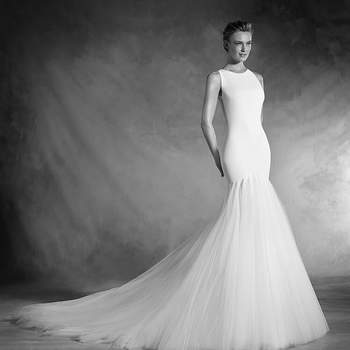 Há vestidos que se transformam numa sensual segunda pele. É o caso deste vestido de noiva sereia de corte baixo e decote redondo justo realizado em crepe, gaza e tule. Um desenho que se cinge à figura e ao mesmo tempo confere volume e movimento à saia.