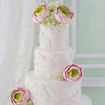 Un diseño romántico y contemporáneo con aplicaciones de encaje en azúcar y bouquet de ranúnculos y hortensias de azúcar.