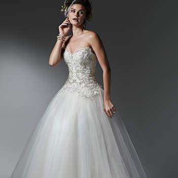 """Camadas leves de tule criam a deslumbrante saia deste vestido com renda e corpete de cristal Swarovski. Acabamento com decote coração e botões de pérola sobre o zíper. <a href=""""https://www.maggiesottero.com/sottero-and-midgley/sigourney/9560"""" target=""""_blank"""">Sottero and Midgley</a>"""