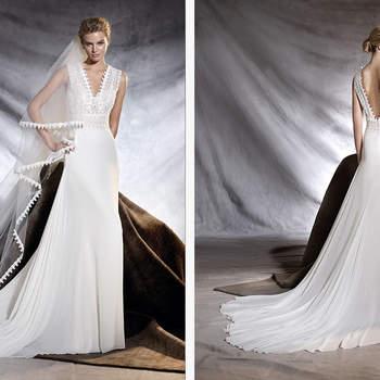Vestido de novia de gasa de talle en la cintura, escote en pico y falda de corte en A. Un modelo de inspiración bohemia con un minucioso trabajo ornamental de guipur en el escote que marca la diferencia.