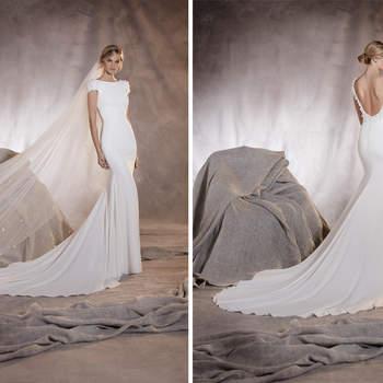 Blumen sind die Stars dieses Meerjungfrauen-Designs in Crepe und Tüll. Ein Hochzeitskleid mit schönen kurzen Ärmeln und Details am Ausschnitt und Rücken.