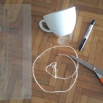 Necesitas: 1 taza blanca de porcelana, unas tijeras, mecate en color crudo, plumón indeleble en color negro y una bolsa de celofán