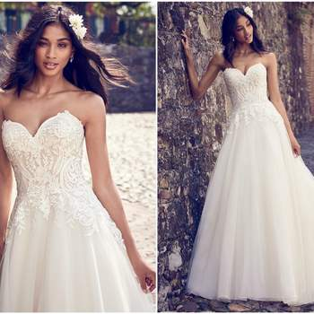 """This sweet and simple wedding dress features a bodice of lace motifs atop a tulle skirt. Complete with strapless sweetheart neckline and lined with shapewear for a figure-flattering fit. Finished with covered buttons over zipper closure.  <a href=""""https://www.maggiesottero.com/maggie-sottero/rayna/11187?utm_source=zankyou&amp;utm_medium=gowngallery"""" target=""""_blank"""">Maggie Sottero</a>"""