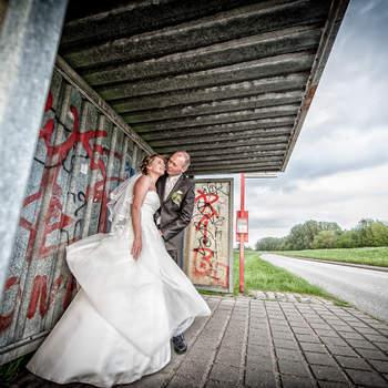 Kommentar des Fotografen: Leider war das Wetter dieses Jahr, zumindest in Hamburg, häufig nicht so toll. Eigentlich hatten wir mit diesem Brautpaar geplant, ein paar schöne Bilder an der Elbe zu machen. Leider war es aber so kalt und windig, dass die Braut unheimlich gefroren hat. Zwischen den Bildern haben wir den beiden immer wieder eine Decke gegeben, um sich aufzuwärmen. Als ich dann diese Bushaltestelle mit Graffitis sah, fand ich den Kontrast so toll und gleichzeitig war es etwas windgeschützt, also haben wir die Bilder dort gemacht.   Mehr von Herrn Schneider auf www.wedding-hamburg.de.
