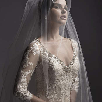 """Stunning lace appliqués trail the skirt of this A-Line wedding dress, complete with illusion lace three-quarter sleeves and V-neckline, adorned with Swarovski crystals. Finished with pearl button over zipper closure.  <a href=""""http://www.sotteroandmidgley.com/dress.aspx?style=5SW074"""" target=""""_blank"""">Sottero and Midgley Spring 2015</a>"""