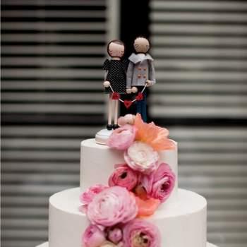 Carino questo cake topper con gli sposini stilizzati che tengono in mano uno stendardo con le loro iniziali