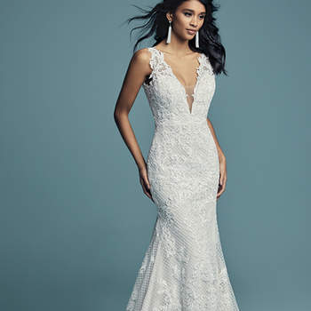 """<a href=""""https://www.maggiesottero.com/maggie-sottero/hailey/11268"""">Maggie Sottero</a>  Lace motifs cascade over crosshatch and tulle in this unique fit-and-flare wedding gown, completing the bodice. Featuring an illusion plunging V-neckline, straps, and square back. Lined with shapewear for a flattering fit, and finished with covered buttons over zipper closure. Detachable tulle overskirt accented with an attached beaded belt sold separately."""