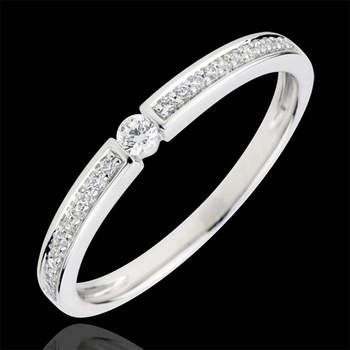 Precioso y atemporal anillo compuesto por un diamante solitario de 0,015 quilates en el centro de una montura asimétrica de oro blanco de 9 quilates pavimentada con 22 diamantes para darle la elegancia de originalidad sutil.  Foto: Edenly.  http://tinyurl.com/ckedsqm