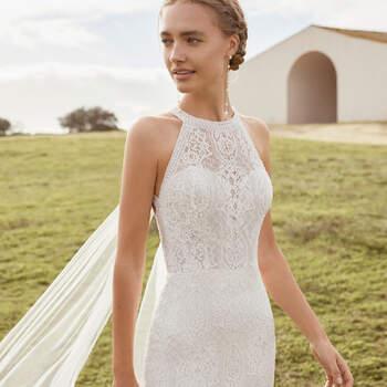 O vestido de noiva Aura exibe uma silhueta de sereia, com um toque sexy e sofisticado, perfeito para um casamento civil mágico, sobretudo na primavera. O encanto exala do corpete, através de uma imponente renda e decote halter, que se destaca por costas completamente aberta com uma capa removível. | Rosa Clará Boheme 2021