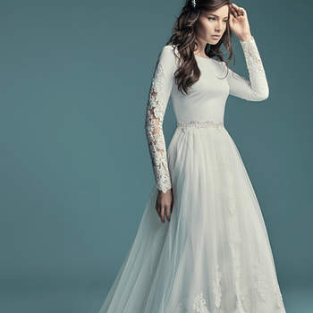 """<a href=""""https://www.maggiesottero.com/maggie-sottero/olyssia/11500"""">Maggie Sottero</a>  This elegant sleeved wedding dress is comprised of Talin Stretch Crepe. Featuring a bateau neckline, scoop back, and lace illusion along the long sleeves. Finished with covered and crystal buttons over zipper closure. Detachable overskirt accented in lace sold separately."""