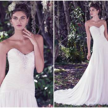 """Ruched tulle emphasizes the ethereal lightness of this feminine A-line wedding dress. Barely-there layers of tulle add dimension to a fitted drop-waist bodice, featuring Swarovski crystals along a soft sweetheart neckline. Finished with covered buttons over zipper and inner elastic closure.   <a href=""""https://www.maggiesottero.com/maggie-sottero/heather/9761"""" target=""""_blank"""">Maggie Sottero</a>"""