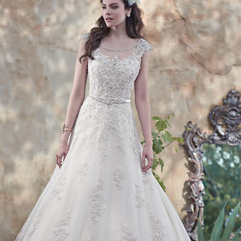 "Glimmering lace appliqués, dotted with Swarovski crystal and pearl embellishments, lay atop tulle in this alluring ball gown, with stunning illusion sweetheart neckline and illusion back. Dainty lace cap-sleeves and a delicate ribbon belt at the waist complete the look. Finished with covered buttons over zipper and inner elastic closure. <a href=""https://www.maggiesottero.com/maggie-sottero/morgan/9512"" target=""_blank"">Maggie Sottero</a>"
