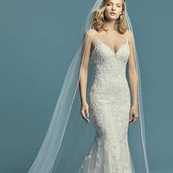 """<a href=""""https://www.maggiesottero.com/maggie-sottero/jolynn/11487"""">Maggie Sottero</a>  Beaded lace motifs cascade over tulle in this soft fit-and-flare wedding dress. Beaded spaghetti straps glide from sweetheart neckline to illusion back accented in lace motifs. Finished with covered buttons over zipper closure. Paired with tulle veil edged in pearls and Swarovski crystals (Charlene, VL8MS694) sold separately."""