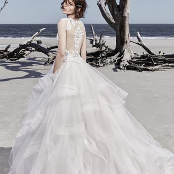 Un moderno vestido que presenta un corpiño de encaje con pequeñas incrustaciones de cristales de Swarovski, sobre una falda de capas de tul.