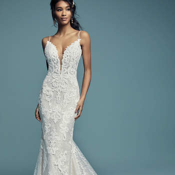 """<a href=""""https://www.maggiesottero.com/maggie-sottero/tuscany-lynette/11514"""">Maggie Sottero</a>  Shimmering lace motifs waltz over allover lace in this romantic sheath wedding dress, comprised of tulle. Beaded spaghetti straps glide from the sheer bodice and illusion plunging sweetheart neckline to sheer back, also layered with lace motifs and allover lace. Finished with covered buttons over zipper closure."""