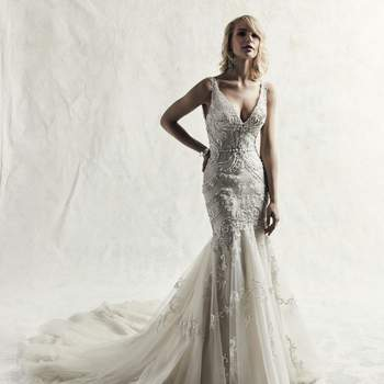 Una sorprendente fusión de glamour y sofisticación, este vestido de novia de corte ceñido con motivos de encaje bordado.