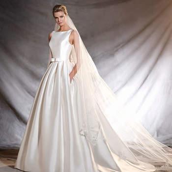 Elegantíssimo vestido de noiva de mikado com decote em barco e voluptuosa saia. Um bonito modelo de silhueta princesa cheio de detalhes preciosistas elaborados com fio bordado e pedraria nas costas. Um gracioso cinto realça a silhueta feminina.