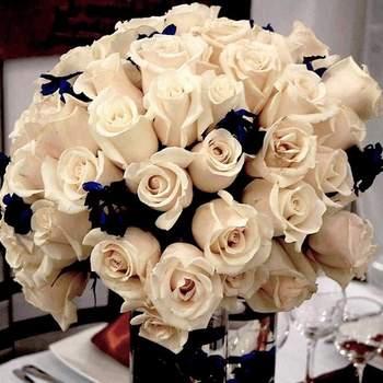 Arreglo floral para mesa con rosas beige y matizadas con otra variedad en azul oscuro.