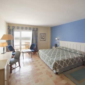 """La modernidad no está reñida con la elegancia, ni tampoco con el bienestar. En tu noche de bodas, querrás disfrutar de espacios exclusivos, pero también de una decoración funcional y relajante que te ayude a descansar. En Paradores han escogido con cuidado los ambientes para garantizar que el buen gusto y la facilidad para el descanso estén presentes en sus suites y habitaciones, como esta del Parador de Ayamonte. Foto: <a href=""""http://zankyou.9nl.de/wdbk"""" target=""""_blank"""">Paradores</a><img src=""""http://ad.doubleclick.net/ad/N4022.1765593.ZANKYOU.COM/B7764770.4;sz=1x1"""" alt="""""""" width=""""1"""" border=""""0"""" /><img height='0' width='0' alt='' src='http://9nl.de/xyl3' />"""