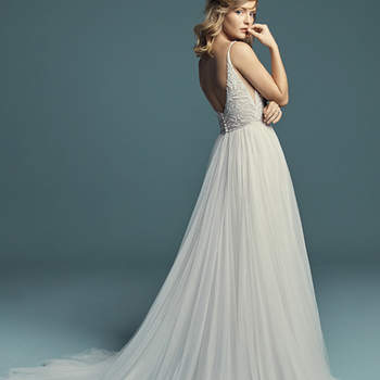 """<a href=""""https://www.maggiesottero.com/maggie-sottero/charlene/11275"""">Maggie Sottero</a>  This vintage-inspired A-line wedding gown features a beaded bodice accented in Swarovski crystals and sheer side insets. Beaded spaghetti straps complete the V-neckline, trimmed in illusion, and scoop back. Sheath skirt comprised of tulle with a princess seam slit. Finished with covered buttons over zipper closure. Tulle veil accented in pearls and Swarovski crystals sold separately."""