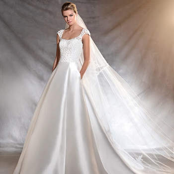 Distinto vestido de noiva de mikado de estética aristocrática. Um clássico de corte na cintura, decote redondo e silhueta princesa. O detalhe: os ornamentos de pedraria e fio bordado que adornam o corpo.