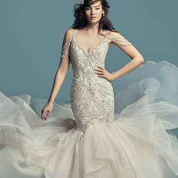"""<a href=""""https://www.maggiesottero.com/maggie-sottero/brinkley/11427"""">Maggie Sottero</a>  Glamorous and vintage-inspired, this mermaid wedding dress features a tulle bodice accented in beaded embroidery and Swarovski crystals. Beaded illusion cold-shoulder sleeves complete the sweetheart neckline and plunging V-back, also trimmed in beading and illusion. Fit-and-flare skirt comprised of tiered Chic Organza trimmed in horsehair. Finished with crystal buttons over zipper closure."""
