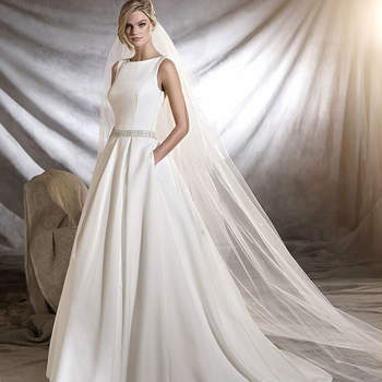 Original vestido de noiva de inspiração clássica estilo princesa. Um modelo de corte na cintura elaborado em piqué, tule e detalhes de pedraria. Destaca-se o belíssimo cinto joia que lhe confere um ar elegante.
