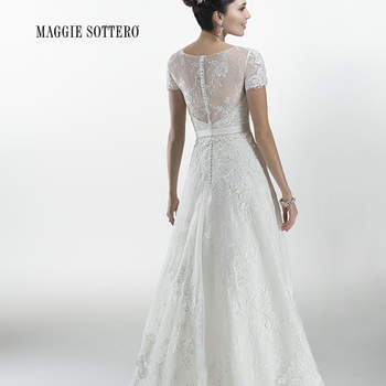 "Lace appliqué and Chantilly lace A-line with detachable satin belt featuring center front bow detail. Finished with covered buttons and zipper over inner elastic back closure. Available with lace appliqué on Chantilly lace short sleeve jacket.  <a href=""http://www.maggiesottero.com/dress.aspx?style=4MS961JK"" target=""_blank"">Maggie Sottero Platinum 2015</a>"