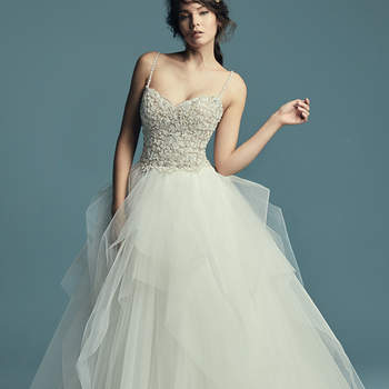 """<a href=""""https://www.maggiesottero.com/maggie-sottero/shauna/11505"""">Maggie Sottero</a>  This elegant princess wedding dress features a beaded bodice with Swarovski crystals atop a tiered tulle ballgown skirt. Beaded spaghetti straps complete the subtle sweetheart neckline. Finished with crystal buttons over zipper closure."""