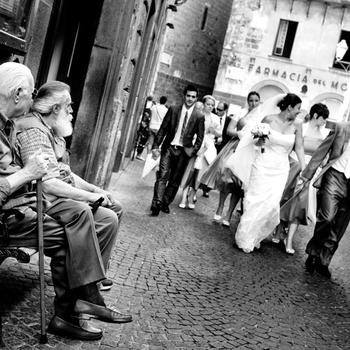 Questa foto rispecchia lo stile reportage perché è uno scatto rubato subito dopo la cerimonia per le vie della cittadina di Orvieto. I due vecchietti che osservano con curiosità gli sposi  rendono questa immagine reale e significativa.  E' questa la tua foto preferita? Lascia un commento qui sotto, votando per la numero 5