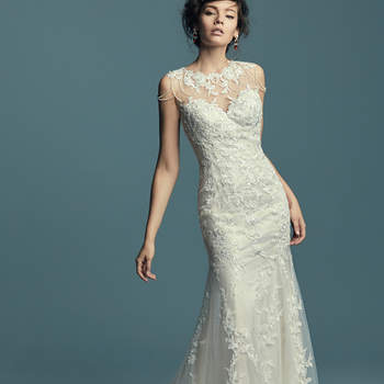 """<a href=""""https://www.maggiesottero.com/maggie-sottero/dorinda/11438"""">Maggie Sottero</a>  This vintage-inspired wedding dress features a unique neckline of beaded lines and lace motifs along the illusion jewel neckline and illusion back. Soft fit-and-flare silhouette features embroidered lace motifs atop tulle. Finished with covered buttons over zipper closure."""