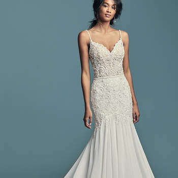 "<a href=""https://www.maggiesottero.com/maggie-sottero/imani/11483"">Maggie Sottero</a>  Embroidered lace motifs accented in pearls and crystals dance over the sheer bodice of this chic boho wedding dress. Beaded spaghetti straps glide from sweetheart neckline to illusion back embellished in lace motifs. Fit-and-flare skirt comprised of Revina Chiffon. Finished with pearl buttons and zipper closure."