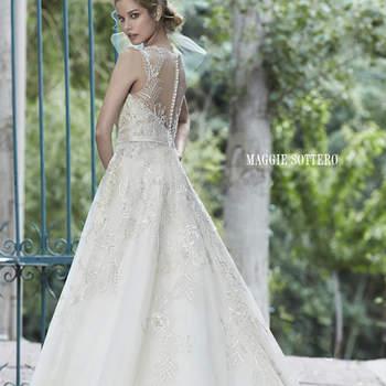 """Este vestido de tul es la representación de la felicidad nupcial. Se complementa el look con cristales de Swarovski deslumbrantes que acentúan el corpiño y escote ilusión, encaje dobladillo festoneado, y el cinturón de satén delicado en la cintura. Acabado con botón de perla sobre la cremallera y cierre elástico interior.  <a href=""""http://www.maggiesottero.com/dress.aspx?style=5MS021"""" target=""""_blank"""">Maggie Sottero Spring 2015</a>"""