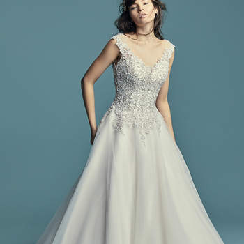 """<a href=""""https://www.maggiesottero.com/maggie-sottero/eden/11469"""">Maggie Sottero</a>  This princess wedding dress features a bodice of beaded lace motifs accented in Swarovski crystals, trailing into a ballgown skirt comprised of tulle. Featuring a scoop neckline, illusion cap-sleeves, and a V-back with pretty lace-up detail. Finished with corset closure and zipper closure."""