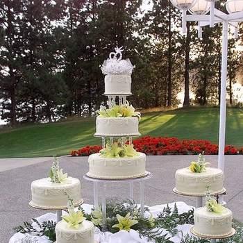 No necesariamente las tortas de boda deben estar una y sobre otra. Tal como lo aprecias en la foto, puedes presentar algunas en torre y el resto de diferentes tamaños rodeando la principal.