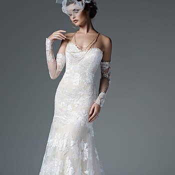"""Linda combinação de renda bordada e tule plumeti criam este vestido de noiva chique, com decote coração e ilusão nas luvas de renda. Acabamento com espartilho interno e botões de pérola sobre zíper. <a href=""""https://www.maggiesottero.com/sottero-and-midgley/alexandra/9584"""" target=""""_blank"""">Sottero and Midgley</a>"""