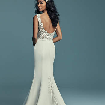 """<a href=""""https://www.maggiesottero.com/maggie-sottero/jayleen/11430"""">Maggie Sottero</a>  This unique wedding dress features a bodice accented in beaded lace motifs, completing the illusion bateau neckline and straps, a sheer scoop back with crosshatch detail. Aldora Crepe fit-and-flare skirt features tulle and lace godets at the sides and back, all accented in lace motifs. Completed with an Aldora crepe belt. Finished with covered buttons and zipper closure."""