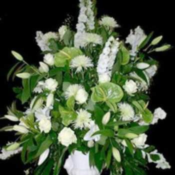 Centre de table mariage Prestige, composition réalisée dans un vase, avec des anthuriums, diverses variétés de fleurs blanches et feuillage. Crédit photo: Atelier floral