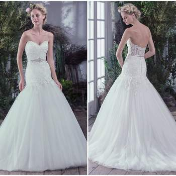 """Ultra-feminine and exquisitely graceful, this drop waist fit and flare wedding dress, with unembellished lace bodice and sweetheart neckline, is finished with a beaded belt. An illusion lace back and voluminous tulle skirt add touches of grandiose romance. Finished with pearl buttons over zipper closure. Beaded motif on tulle belt featuring Swarovski crystals sold separately.  <a href=""""https://www.maggiesottero.com/maggie-sottero/oksana/9712"""" target=""""_blank"""">Maggie Sottero</a>"""