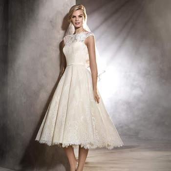 Doce e feminino. Este vestido de noiva curto de inspiração vintage é uma opção romântica para uma cerimónia diurna. O modelo com decote em barco e corte na cintura apresenta um harmonioso desenho de renda que percorre todo o corpo da noiva.