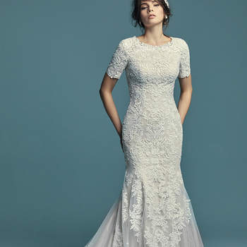 """<a href=""""https://www.maggiesottero.com/maggie-sottero/della-marie/11467"""">Maggie Sottero</a>  Lace appliqués dance over tulle in this chic fit-and-flare wedding dress, featuring an illusion double train trimmed in lace. Complete with jewel neckline and modest quarter-length sleeves. Finished with covered buttons over zipper closure."""